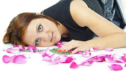 Girl lying in rose petals Stock Photography