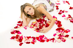 Girl lying with rose petals Royalty Free Stock Photos
