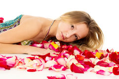 Girl lying in rose petals Royalty Free Stock Images