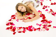 Girl lying with rose petals in view of the heart Stock Photo