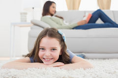 Girl lying on rug while mother relaxing at home Stock Images