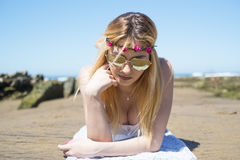 Girl lying on the sand at the beach with sunglasses heard shaped Stock Photography