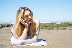 Girl lying on the sand at the beach with sunglasses heard shaped Stock Image