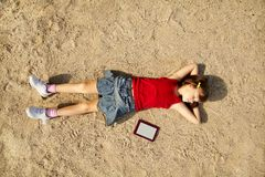 Girl lying on the sand Stock Photography