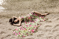 Girl lying on the sand Stock Image