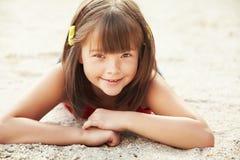 Girl lying on the sand Stock Photos