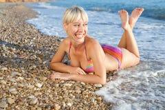 Girl lying in sea foam Royalty Free Stock Photography
