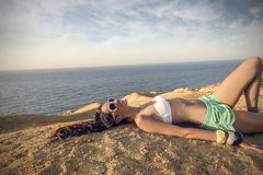 Girl lying at the seaside Stock Images