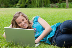 Girl lying on the side in a park while typing on h Stock Image