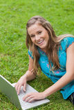 Girl lying on the side while using her laptop Stock Photo