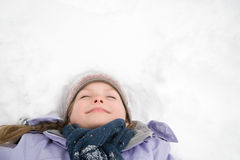 Girl lying on snow Royalty Free Stock Images