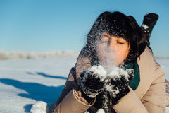 Girl lying on the snow and blows snow from hands Stock Photos