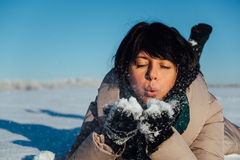 Girl lying on the snow and blows snow from hands Royalty Free Stock Images