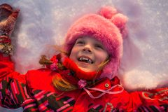 Girl lying in the snow and smiling Stock Image
