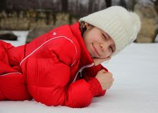 Girl lying in the snow and squinting in the bright white light Royalty Free Stock Images