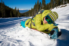 Girl lying on snowboard Royalty Free Stock Images