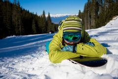 Girl lying on snowboard. Young woman has a rest against forest and slope royalty free stock images