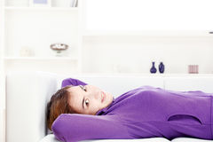 Girl lying on sofa at home Royalty Free Stock Image