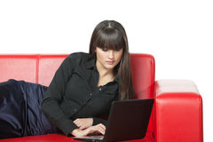 Girl lying on the sofa with laptop Royalty Free Stock Images