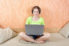 Girl lying on sofa in livingroom  with laptop Royalty Free Stock Photo