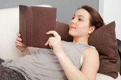 Girl lying on sofa and reading book Royalty Free Stock Photography