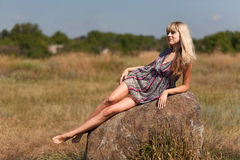 The girl lying on a stone. The girl in a dress lies on a stone in the field in the summer Royalty Free Stock Photography