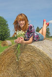 Girl lying on straw bale Royalty Free Stock Photo