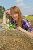 Girl lying on straw bale Stock Image