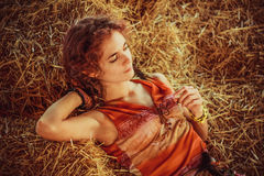 Girl lying in the straw. Beautiful girl lying on the boards straw Royalty Free Stock Photo