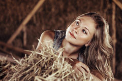 Girl lying in the straw. The girl in the straw rests and looks in the side Royalty Free Stock Image