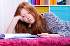 Girl lying and studying. Teenage girl lying in her room and studying hard Royalty Free Stock Photos