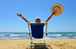 Girl lying on a sun lounger on sandy beach. Royalty Free Stock Photos