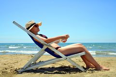 Girl lying on a sun lounger on sandy beach. Royalty Free Stock Photos