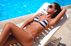 Girl lying and sunbathing by the pool. Wearing swimsuit with stripes Stock Photos