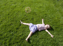 Girl lying supine on grass Royalty Free Stock Photography