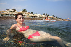 Girl lying in surf Mediterranean Sea, background of beach lounge Stock Photography