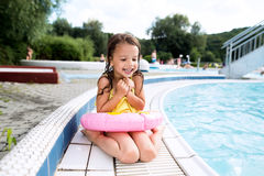 Girl lying by the swimming pool. Summer heat and water. Cute little girl in swimsuit and inflatable ring lying sitting by the swimming pool. Summer heat and Stock Images