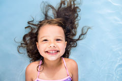 Girl lying in swimming pool. Summer heat and water. Cute little girl in swimsuit lying in swimming pool, smiling. Summer heat and water Stock Photography