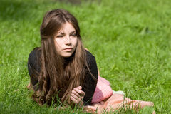 Girl lying in th park. Attractive girl is lying on the grass in the park, starring to the infinity and thinking Royalty Free Stock Photos