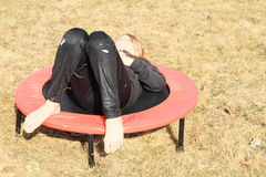 Girl lying on trampoline. Bare soles of feet of little girl - barefoot kid in black clothes lying on black and red kids´ small trampoline standing on grass of Stock Image