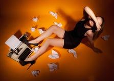 Girl lying beside the typewriter royalty free stock image