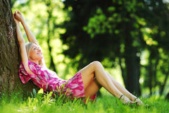 Girl lying under a tree Stock Photography
