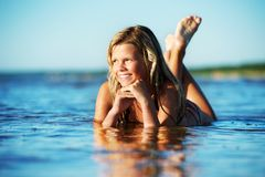 Girl lying in the water Stock Photos