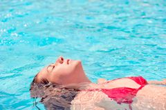 Girl lying on the water with eyes closed in the pool Royalty Free Stock Photography