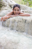 Girl lying in a waterfall Royalty Free Stock Photos
