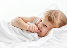 Girl lying in white bed Royalty Free Stock Photography