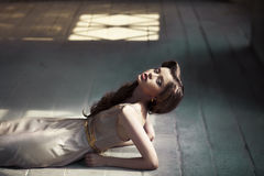Girl lying on a wooden floor Stock Images