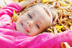 Girl lying on yellow leaves Royalty Free Stock Photo
