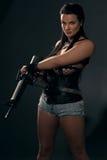 Girl with machine gun on dark background Stock Photos