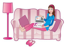 Girl with a magazine on a sofa Stock Photos